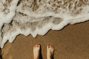 海岸線の砂浜で素足