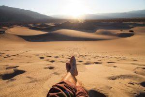 砂漠で素足でくつろぐ