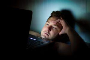 暗闇でパソコンを見る男性