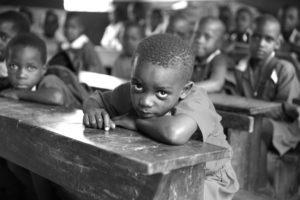 寝ながら授業をうける少年